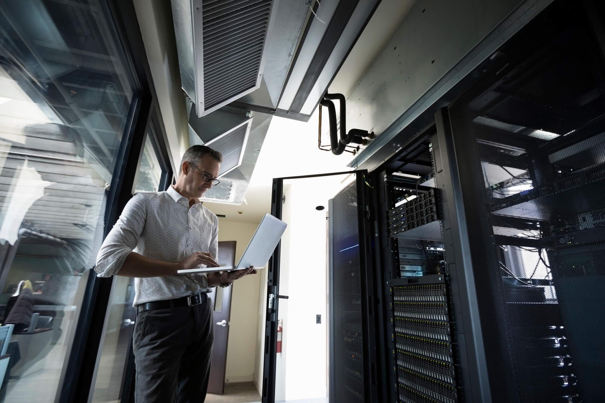 Male Caucasian IT technician using laptop in server room